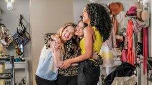 Kuvassa kolme naista halaa toisiaan.