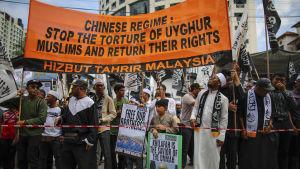 Människor demonstrerar för uigurers rättigheter i Malaysia.