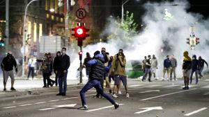 På bilden gata i Belgrad där demonstranter springer. De omges av rök.