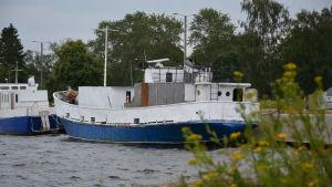 En blåvit, medelstor båt ligger vid en kaj.
