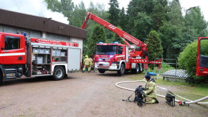 Två brandbilar och brandmän bredvid ett rykande hus.