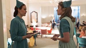 På bilden syns skådespelarna Sarah Paulson och Alice Englert iklädda sjuksköterskeuniformer från 1950-talet. De står och tittar på varandra och i bakgrunden syns en pampig salong.