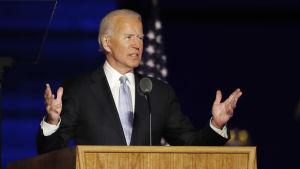 Yhdysvaltain presidentiksi valittu Joe Biden nostaa käsiää sivuille puhuessaan.