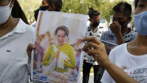 Demonstranter visar upp bilder av den fängslade Aung San Suu Kyi under en protest utanför FN:s högkvarter i Bangkok i Thailand.