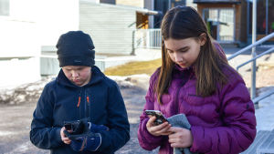 Två skolbarn tummar på sina telefoner.