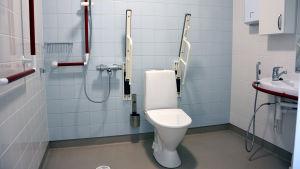 Ett handikappvänligt badrum där det finns en dusch, toalett och ett handfat.