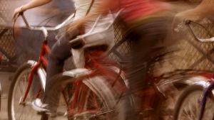 Tre cyklar i rörelseoskärpa (ser ut som att de far hårt framåt) på en gata.