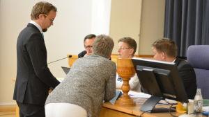 Palaver med flera ledamöter runt ordföranden under fullmäktigemöte.