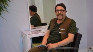 peter bergfeldt sitter i en stol i hans och ginas frisörsalong