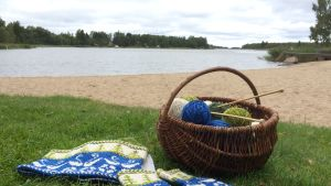 halsvärmare, handledsvärmare och korg med garn på gräsmatta vid stranden med havet i bakgrunden.