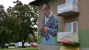 En äldre man i blå skjorta har målats på väggen. Han håller en bok med pip i sin hand.
