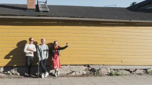 Kolme henkilöä nojaa keltaiseen lautaseinään ja ottaa selfie-kuvaa yhdessä (kuvassa Henri Ylikulju ja Egenland-ohjelman juontajat Nicke Aldén ja Hannamari Hoikkala)