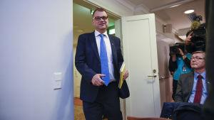 Statsminister Juha Sipilä gör entre vid presskonferens