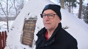 Erik Liljeström framför en snötäckt minnessten för pellingeslaget