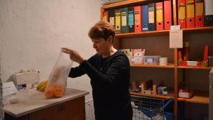 May Ahlqvist packar upp en påse med mandariner.