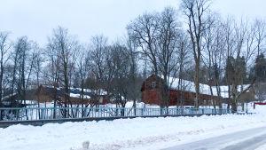 En vintrig vy över ett område med gamla byggnader, mycket snö, bilden tagen från en bro, vägen och broräcket syns i förgrunden. Bara träd.