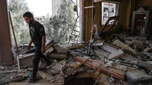 Man går omkring i ett förstört hus i Douma, Syrien.