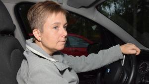 En kvinna sitter bakom ratten i en personbil. Mörkt ute. Hon ser fundersam ut.