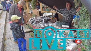 En man och ett barn pratar med en fiskeförsäljare på Strömmingsmarknaden.