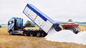 En lastbil tömmer ett stort lass vittpulver på en åker.
