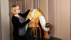Maria Linden med en skyltdocka iklädd folkdräkt.
