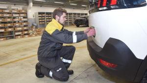 Alexander Laurila sätter fast registerskylten på en bil.