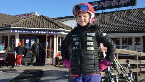 Ellen Fröjdö, en ung flicka med svart jacka, ljusröd hjälm och skidglasögon, står framför en kafeteria på ett skidcenter.