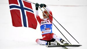 Therese Johaug ligger i snön med Norges flagga