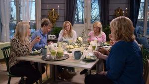En grupp kvinnor som sitter och äter runt ett bord. De firar en baby shower.