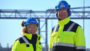 Arno Avela och Tarja Korvenoja ler. De har gula jackor på sig och blå bygghjälm på huvudet. Soligt väder.