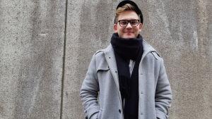 ung man i grå kappa och svart halsduk och svart skärmmössa och glasögon står och ler med händerna i fickorna mot en hög grå vägg