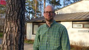 man i grön skjorta invid trädstam