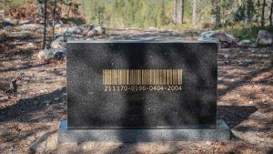 Mustan hautakiven näköinen taideteos, kultainen viivakoodi
