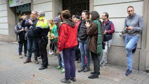 Knappt tjugo personer har samlats på en trottoar i Barcelona för att diskutera.
