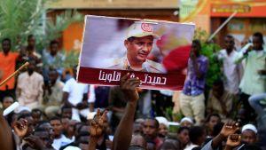"""Mohamed Hamdan Dagalo """"Hamidati"""" är kommendör för milisgruppen RSF och nu en central gestalt också i det styrande militärrådet. Här bärs hans porträtt fram av demonsranter som demonstrerade till stöd för militärrådet den 31 maj."""