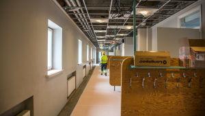 Byggkarl går i lång skolkorridor