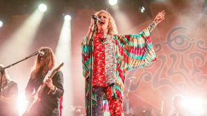 Vaaleahiuksinen laulaja Ellips Ruisrockin lavalla värikkäissä vaatteissaan värikkään seinävaatteen edessä. Hän laulaa silmät kiinni ja toinen käsi ilmassa. Taustalla pitkähiuksinen kitaristi.