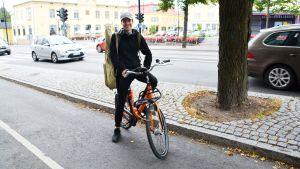 Man står vid en orange stadscykel i Borgå centrum.