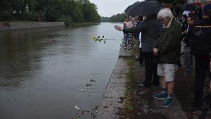 Människor samlade för en minnesstund vid Aura å. Några kastar blommor på vattnet.