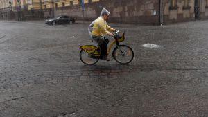 En cyklist cyklar genom ett kraftigt regn på Senatstorget i Helsingfors.