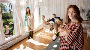 Fyra personer står inne i ett soligt vardagsrum med långa vita gardiner. Utanför på gräsmattan står en man och tittar in genom fönstret.