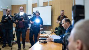 Reportrar filmar och fotar utredningsledaren Olli Töyräs i tingsrätten i Kuopio.
