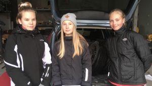 Amelie Levin, Tinja Vainio och Ida Andersson står vid bakluckan till en bil.