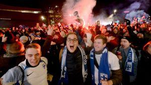 Många fans som firar, tre stycken glada män i förgrunden med matchhalsdukar i Finlands färger.