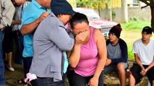 En kvinna böjer sig uppgivet framåt med ansiktet i handen. En person kramar om henne från sidan för att trösta