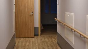 En korridor med ljust golv och dörrar på vardera sida.