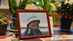 Ett fotografi på en kvinna står på ett bord med blommor bredvid sig.