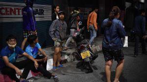 Personer sitter på trottoarkanten i Korat i Thailand.