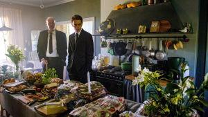 Nisse (Peik Stenberg) och Stefan (Martin Paul) står vid ett långbord fullt med smörgåsar och blommor.
