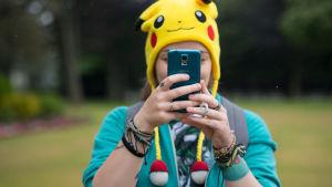 En person med en gul mössa föreställande pokemonen pikachu. Personen håller en telefon framför ansiktet.